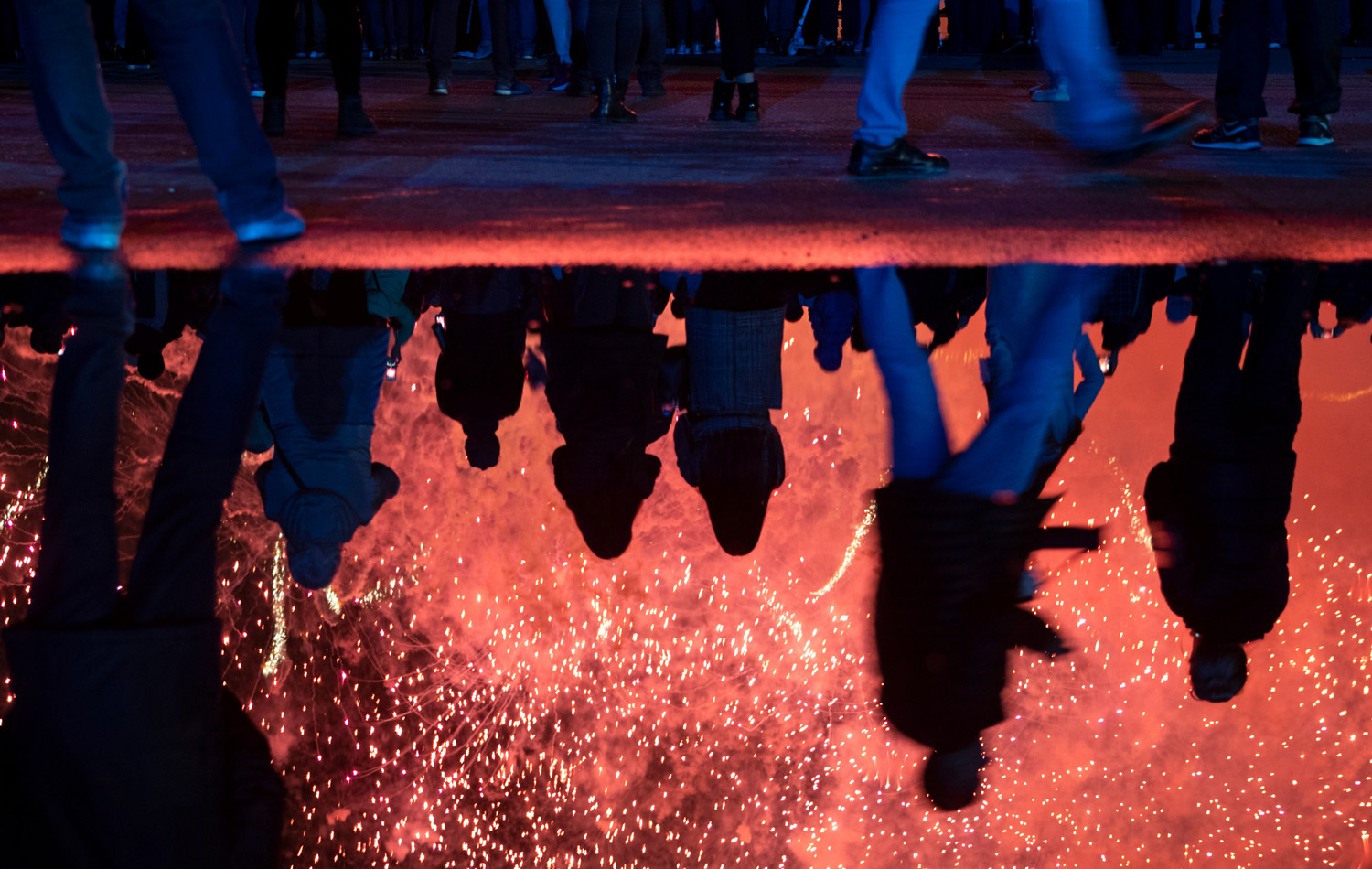 Spectators are reflected in a puddle as they watch fireworks at the International show Circle of Light in Moscow