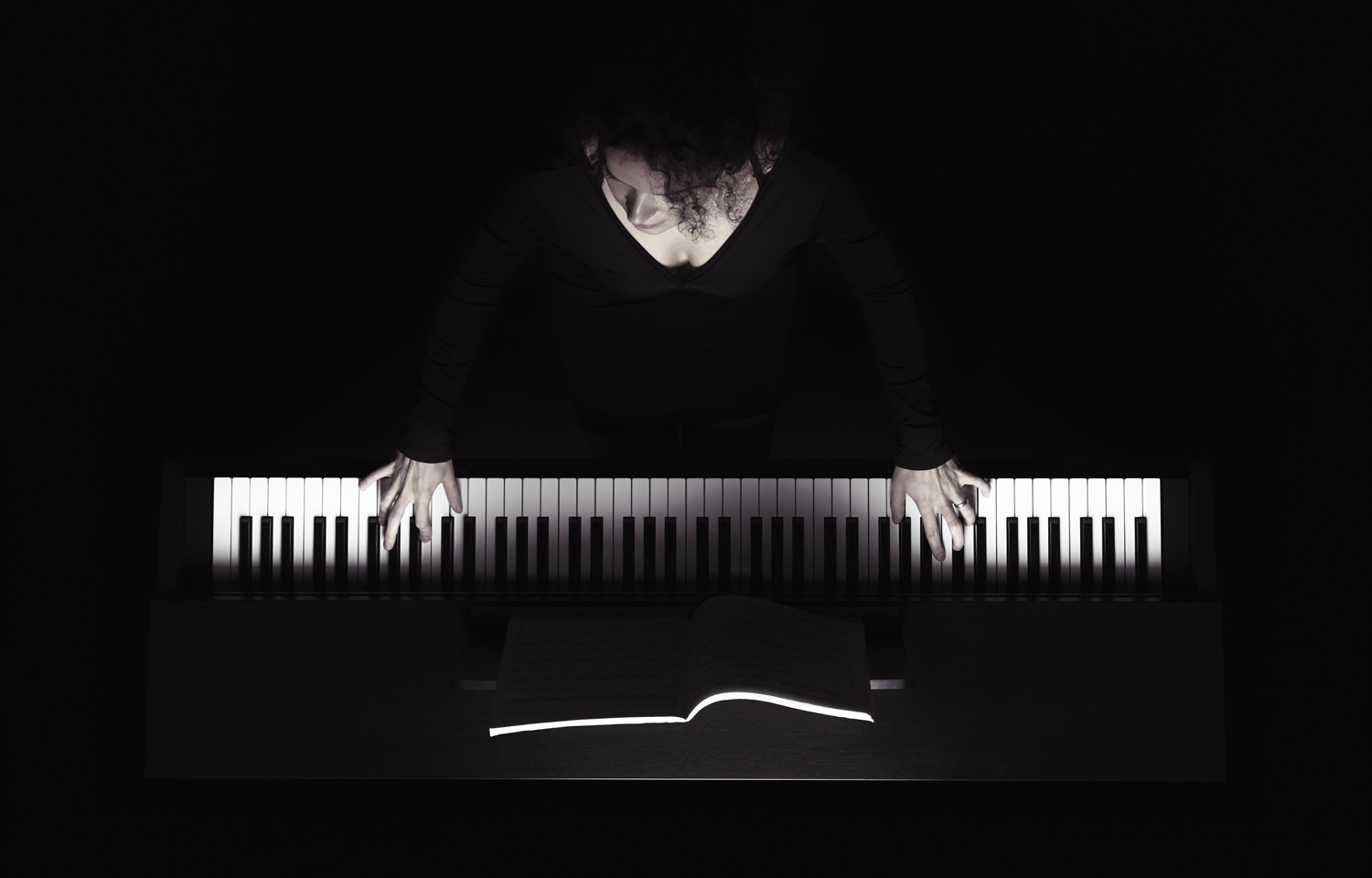 Woman playing the piano, white keys and hands on black background, overhead view in dramatic light — iblalx04436653.jpg