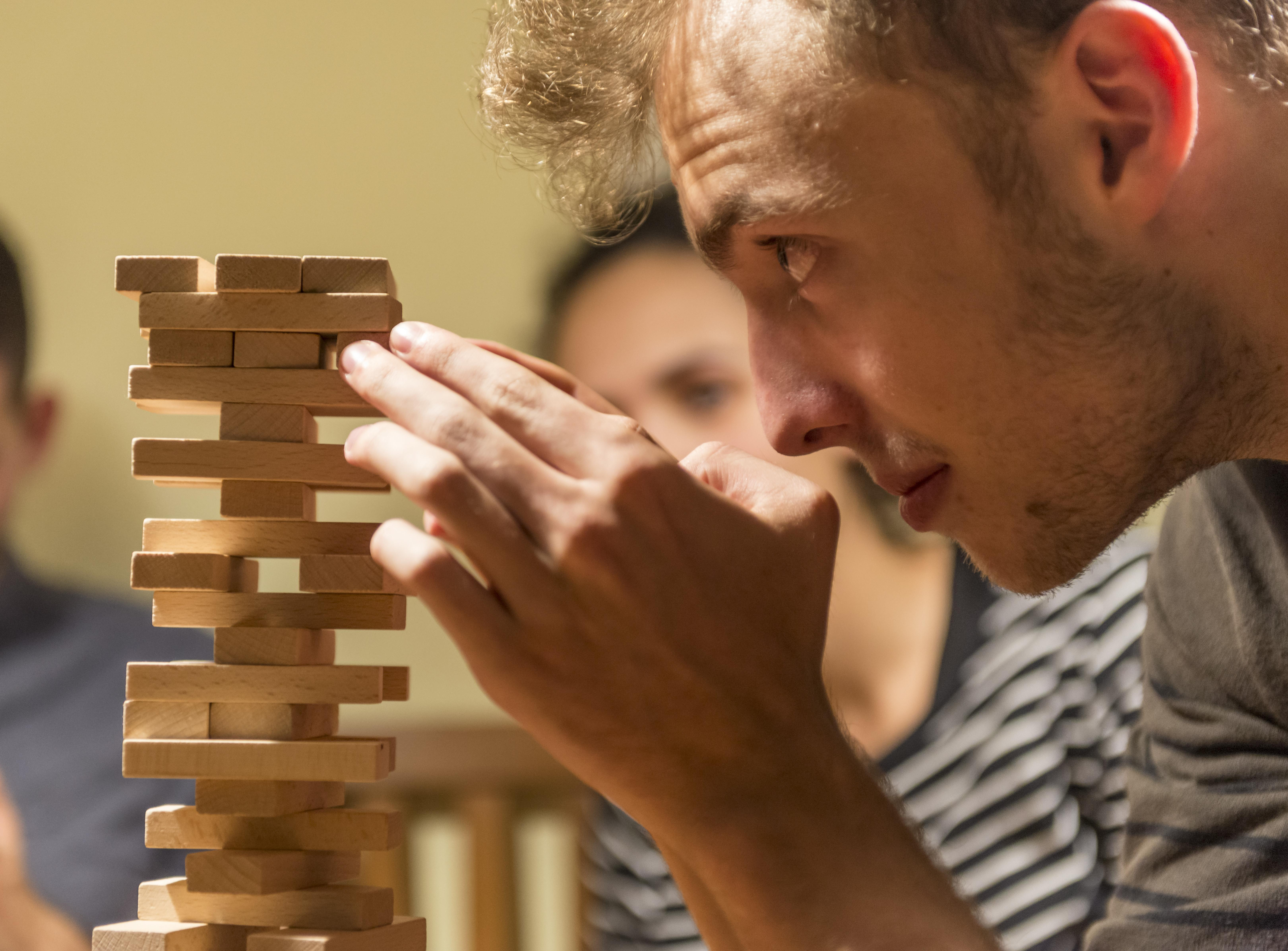 Young man plays Jenga, stacking a tower with wooden blocks, concentrated — ibxmmw04593472.jpg